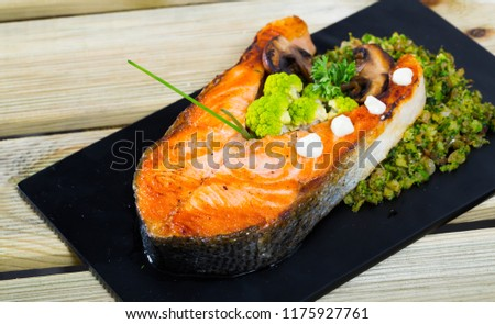Grilled steak of salmon served with steamed broccoli and mushrooms on black serving board  #1175927761
