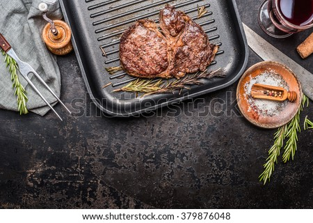 Grilled steak on grill pan with rosemary and spices , dark rustic metal background, top view, place for text, border