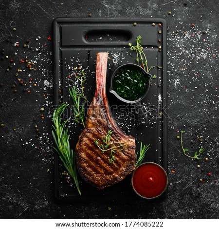Grilled steak on the bone. Tomahawk steak on a black stone background. Top view. Free copy space.