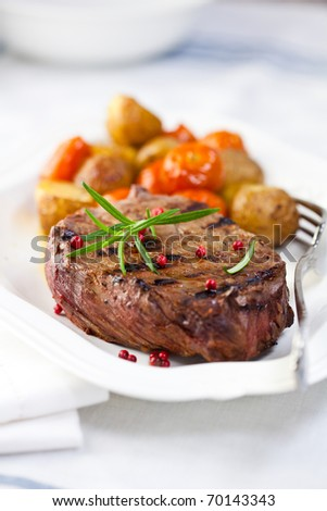 Grilled steak with baked vegetables and fresh rosemary. Concept for a tasty and healthy meal. Close up #70143343
