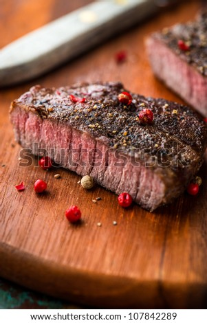 Grilled steak with peppercorns on wooden chopping board