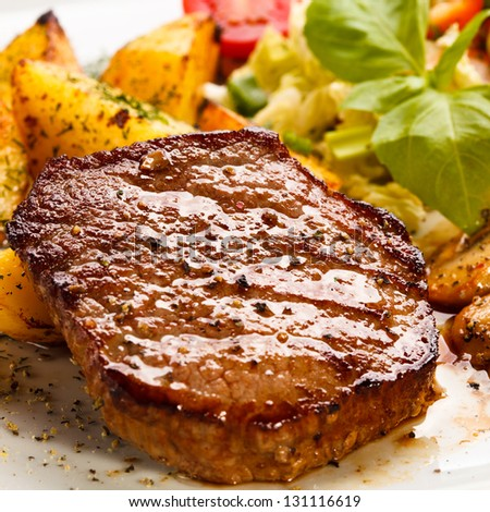 Grilled steaks, baked potatoes and vegetable salad