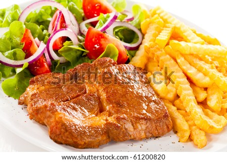 Grilled steaks, chips and vegetable salad