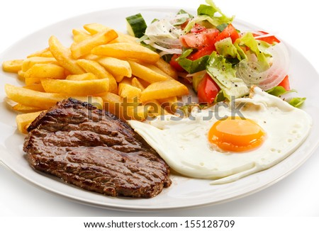 Shutterstock Grilled steaks, French fries, fried egg and vegetables