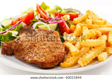 Grilled steaks with fries and vegetable salad