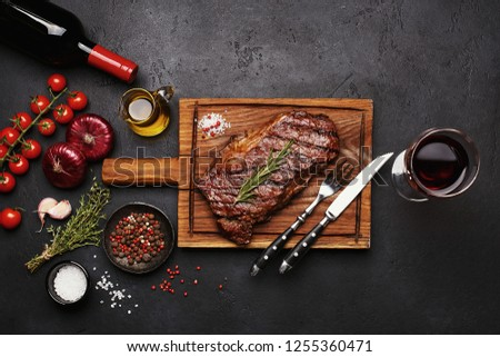 Grilled Striploin beef steak on wooden board with bottle and glass of red wine, vegetables, herbs and spices on dark stone background. Top view #1255360471