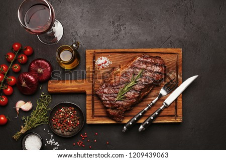 Grilled Striploin beef steak on wooden board with glass of wine, vegetables, herbs and spices on dark stone background. Top view #1209439063