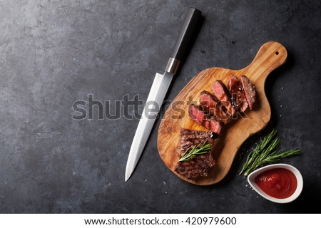 Grilled striploin sliced steak on cutting board over stone table. Top view with copy space