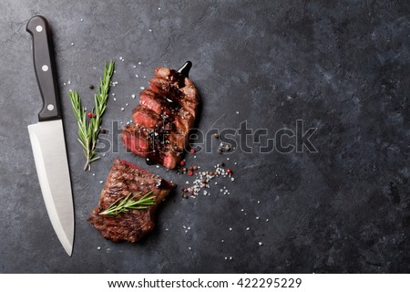 Grilled striploin sliced steak with salt and pepper and knife over stone table. Top view with copy space