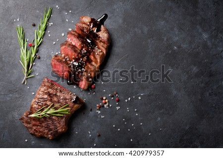 Grilled striploin sliced steak with salt and pepper over stone table. Top view with copy space