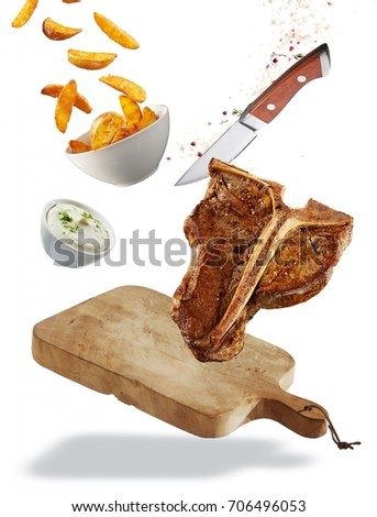 Grilled T-bone steak floating ingredients concept with a chopping board, healthy lean steak, French fries and tzatziki in bowls, spices and a sharp knife isolated on white