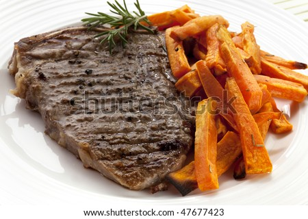 Grilled T-bone steak with oven-baked sweet potato fries.