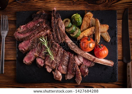 grilled tomahawk ribeye steak on black stone plate
