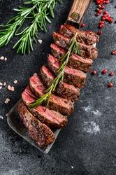 Grilled top blade, Denver steak. Marble meat beef. Black background. Top view
