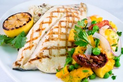 Grilled Trout and Butternut Squash: Gourmet barbecued grilled trout with grill marks and a side vegetable salsa and rice on a white plate.
