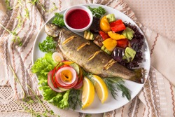 Grilled trout, carp and mullet. Juicy delicacy fish on a plate with a salad of fried vegetables. Balkan cuisine. Restaurant menu