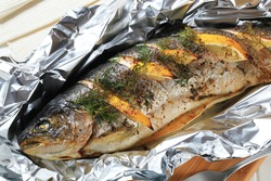 Grilled trout with herbs and lemon on aluminium foil