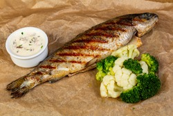 Grilled trout with sauce and broccoli