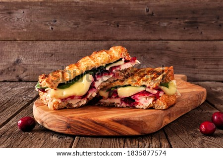 Grilled turkey, cranberry and brie sandwich. Side view on a serving board against a dark wood background. Сток-фото ©