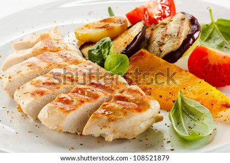 Grilled turkey fillet with vegetables on white background