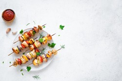 Grilled vegetable and chicken skewers with  bell peppers, zucchini, onion and mushrooms on white background, top view, copy space. Meat and vegetables kebabs on skewers.