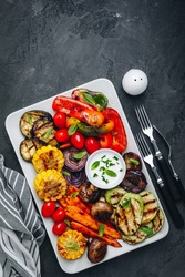 Grilled Vegetable Platter with Zucchini, mushrooms, eggplant, carrots, pepper bell, tomato, onions, corn, and Yogurt Mint Sauce. Top view.