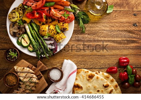 Grilled vegetables and chicken on wooden table overhead shot