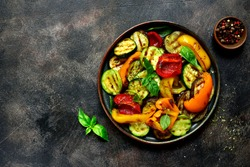 Grilled vegetables (  colorful bell pepper, zucchini, eggplant ) with basil and dry herbs on a plate over dark slate, stone, concrete or metal background.Top view.