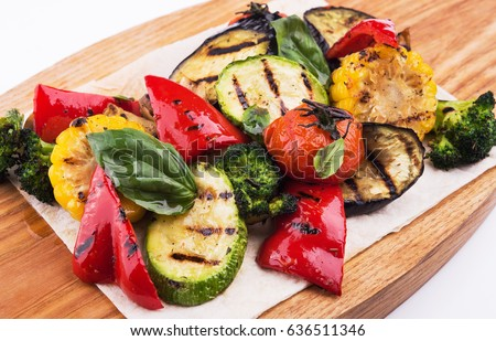 Grilled vegetables on cutting board isolated on white background