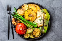 Grilled vegetables - tomatoes, asparagus, zucchini, bell pepper, pineapple slices and garlic on cast iron black plate, gray slate background. top view