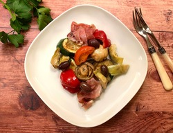 Grilled vegetables with raw ham, zucchini, eggplant, mushrooms, tomatoes, artichokes, olives and red bell peppers. Mediterranian food concept.