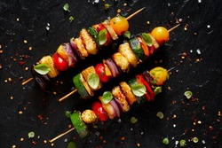 Grilled vegetarian skewers with halloumi cheese and mixed vegetables on black background, top view