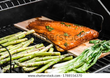 Grilled veggies on a charcoal grill. Asparagus and onions caramelizing. Salmon on a cedar wood plank grilling and smoking.