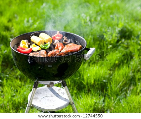 Grilling at summer weekend. Fresh meat and vegetables preparing on grill.