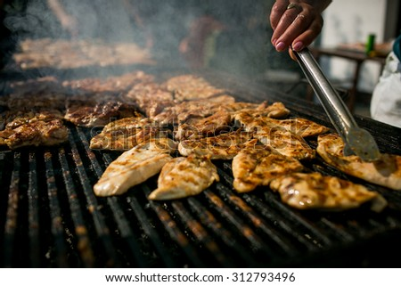 Grilling meat with barbecue stuff. Horizontal shot