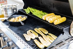 Grilling organic fresh vegetables on an outdoor gas grill in the Summer.