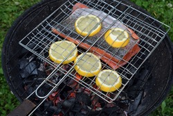 Grilling salmon with lemon slices on round charcoal grill with gridiron. Hot glowing embers under fish.