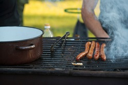 Grilling sausages outdoor on a gridiron over charcoal fire