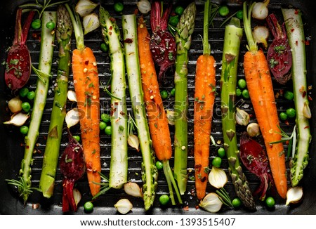 Grilling vegetables, raw vegetables prepared for grilling with the addition of olive oil, herbs and spices located on the grill plate, top view. Healthy nutrition concept, vegan meal