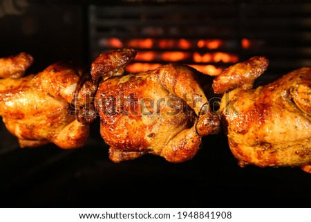 Grilling whole chickens in rotisserie machine, closeup