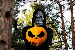 Grim reaper holding halloween pumpkin head. Man in death mask with fire flame in eyes on nature forest trunk background. Halloween holiday concept. Dark horror.