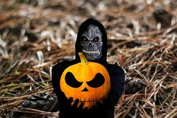 Grim reaper holding halloween pumpkin head. Man in death mask with fire flame in eyes on nature brown pine forest floor background. Halloween holiday concept. Dark horror.