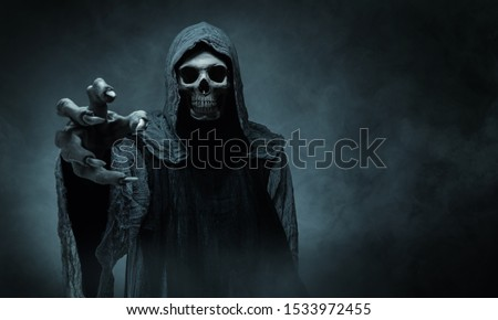 Grim reaper reaching towards the camera over dark background with copy space Stockfoto ©