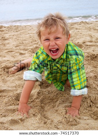 grimacing boy on the beach