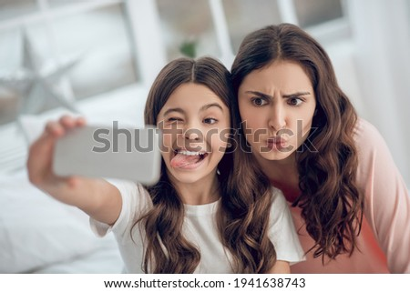 Grimacing funny daughter with mom taking selfie Сток-фото ©