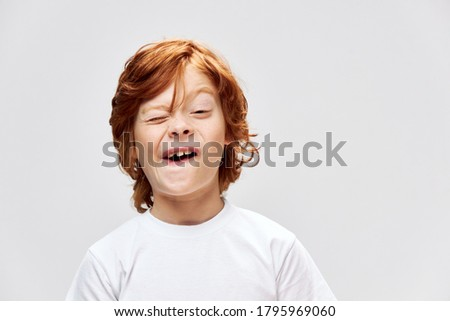 grimacing redhead boy with open mouth squints eyes cropped view gray  Сток-фото ©