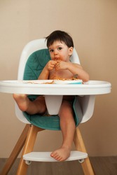Grimy baby boy eating Italian pasta, which hangs out of his mouth, sitting on a high chair against a neutral background.