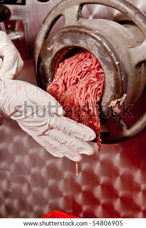 Grinding the mill pork ham. - stock photo