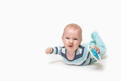 Grinning baby boy is lying on white background holding a toy. Photo contains a lot of free space for your use. All potential trademarks are removed.