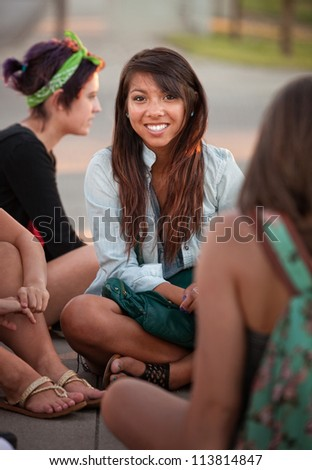 Grinning Filipino girl with friends sitting cross legged